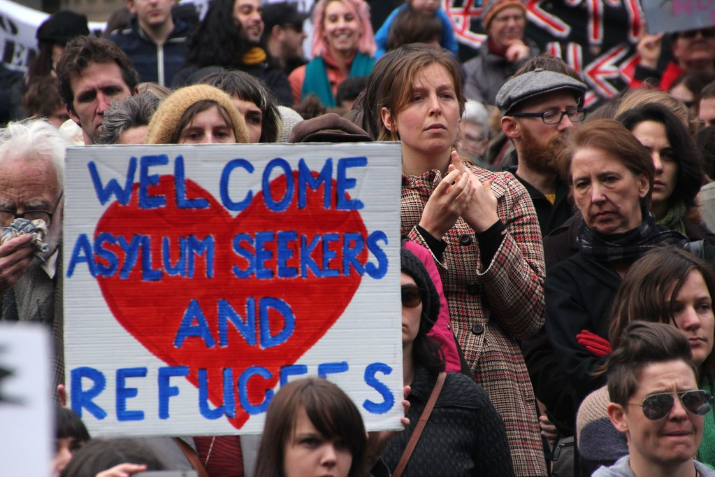 """A crowd of activists. One holds aloft a sign reading """"WELCOME ASYLUM SEEKERS AND REFUGEES"""" in a large red heart in blue text."""
