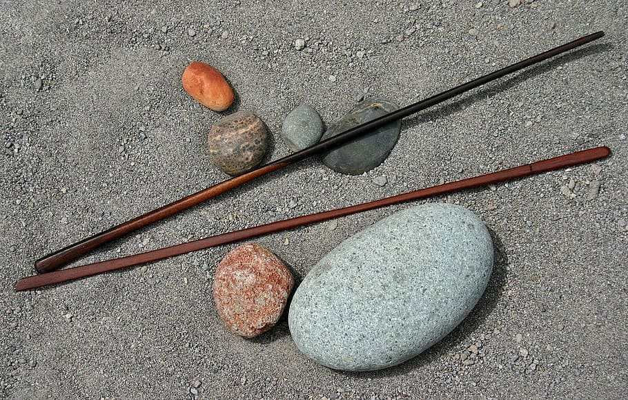 Two sticks and some pretty, colourful stones lie together in damp sand.