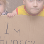 """Two young children hold up a sign that reads """"I'm hungry."""""""
