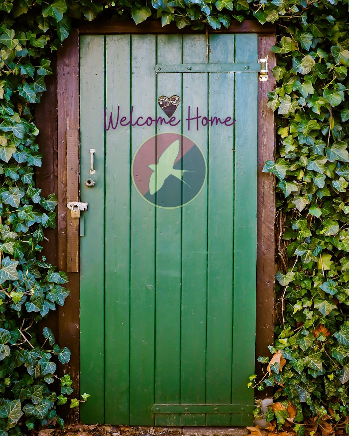"""A green wooden door cozily nestles into green creeping foliage. The Harmony Party UK logo, a white swallow soaring on a red and black bisected circular background, is just above central on the door. Above it are the words """"Welcome home"""" in purple, and above those words in the door is a small heart-shaped inset."""